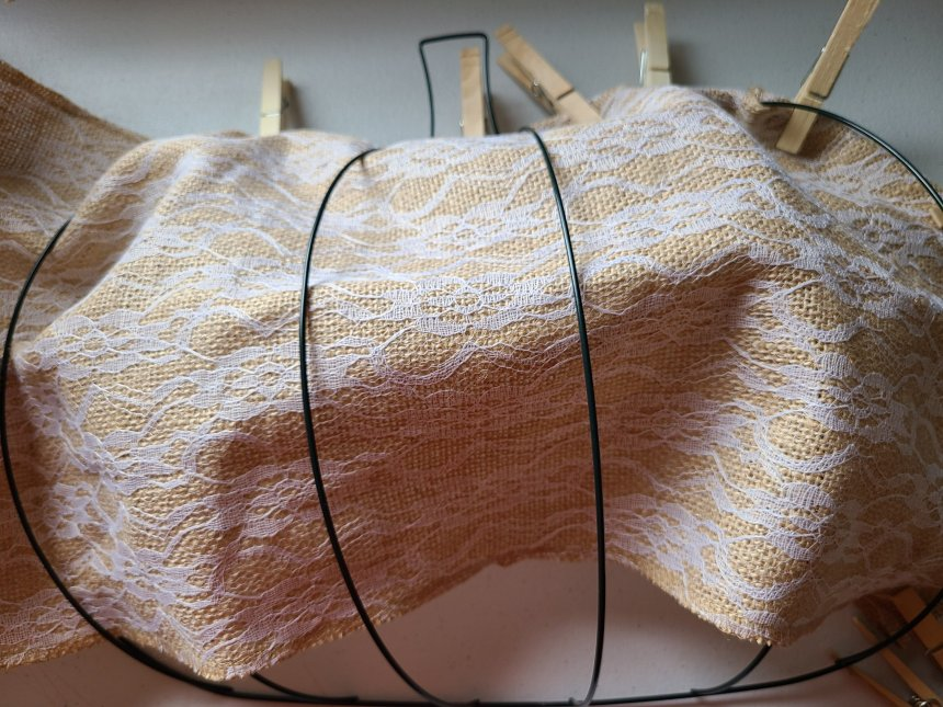 Shows the finished running of the burlap over and under the wire form. Also shows clothespins  holding the edges in place.