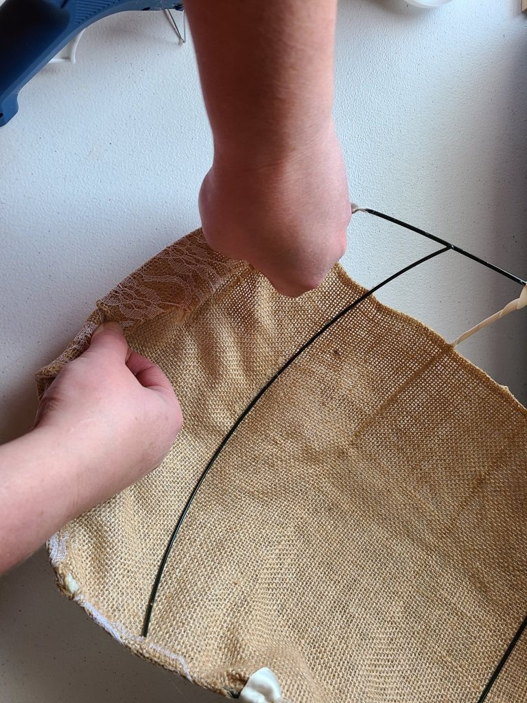 Wrap the end of the burlap around the outside of the form, place hot glue on the wire while pressing it down as you go.