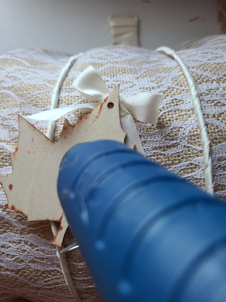 This picture shows how to place the hot glue on the wooden leaf and center it on the front of the completed wreath form.